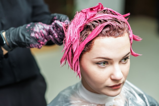 De handen van de kapper brengen roze kleur aan op het haar van de klant.