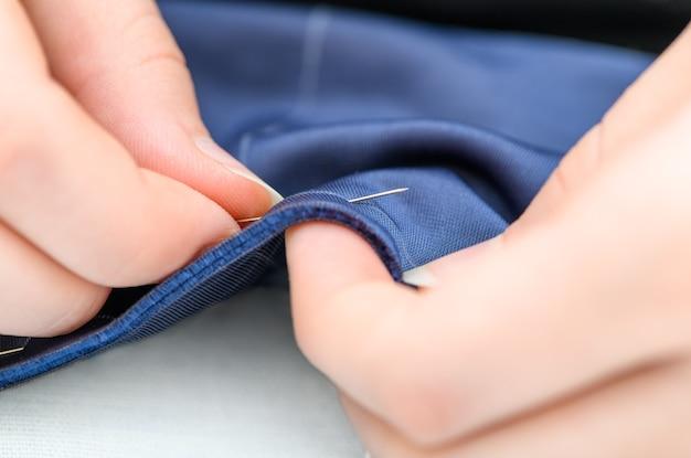 De handen van de kleermaker aan het werk bij het naaien van een blauw stoffenproduct