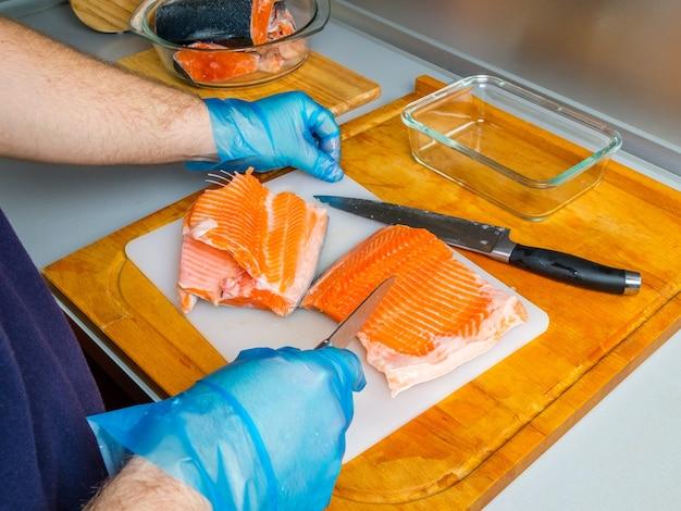 De handen van de kok scheiden de zalmfilets van de botten met een mes