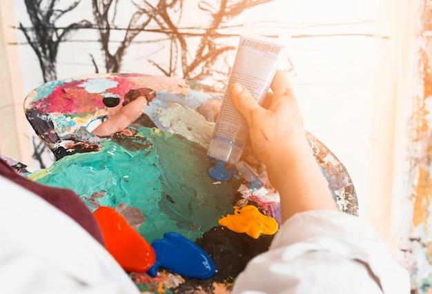 De handen van de kunstenaar knijpen de verf uit de tube op het palet