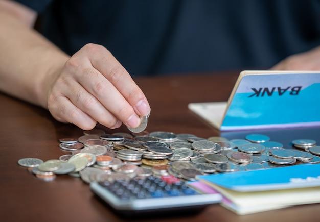 De handen van de mannen die een bankboekje vasthouden en een begroting weven.