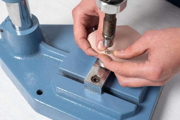 De handen van de meester maken gaten voor de knoppen op een speciale installatiepers