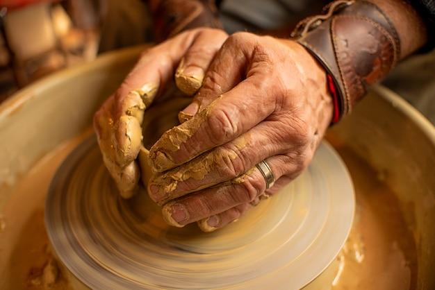 De handen van de meesterpotter staan op een klein kleiproduct dat zich op een speciale machine bevindt