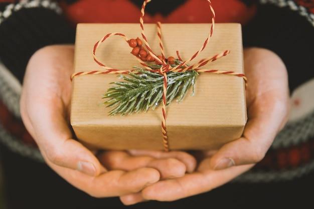 De handen van de mens houden de doos van de kerstmisgift. vrolijk kerstfeest