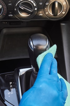 De handen van de mens in blauwe beschermende handschoenen vegen versnellingspook met een doek