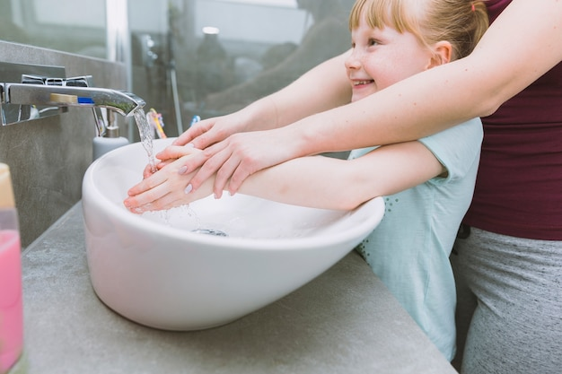 De handen van de moeder van het gewas wassen van vrolijke dochter