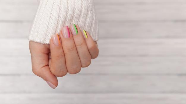 De handen van de mooie verzorgd vrouw met gekleurde spijkers