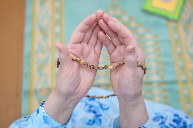 De handen van de moslimvrouwen met hun rozenkransen