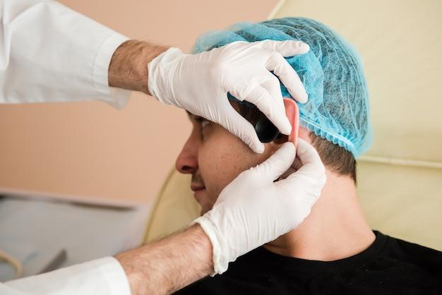 De handen van de otolaryngoloog controleren het oor van de patiënt