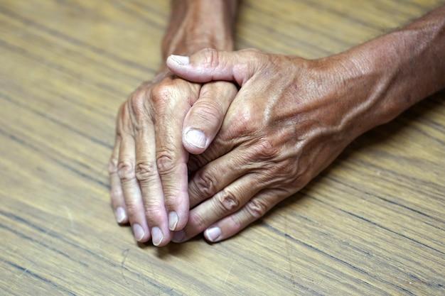 De handen van de oude man op de tafel