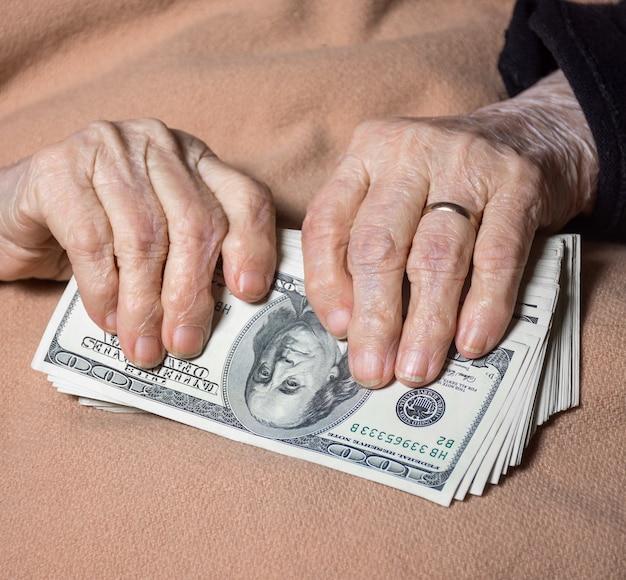 De handen van de oude vrouw die thuis contant geld in dollars houden
