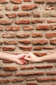 De handen van de paarholding tegen bakstenen muur