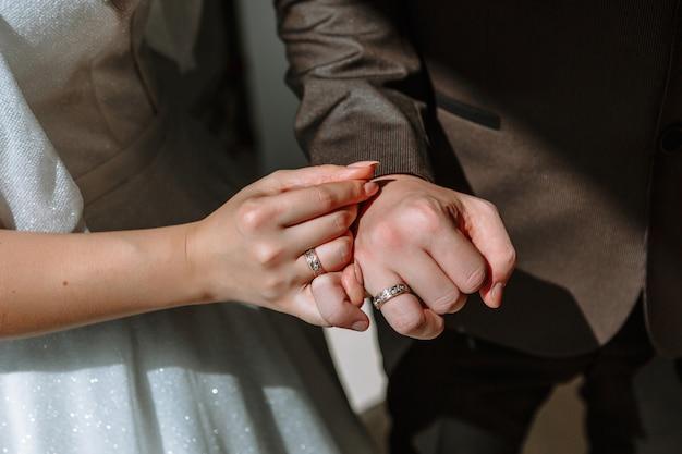 De handen van de pasgetrouwden, die trouwring dragen
