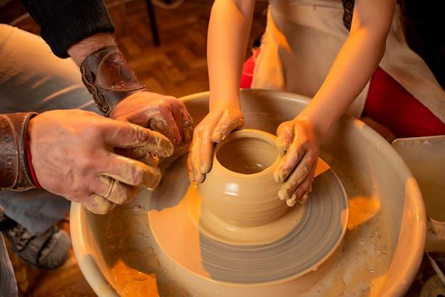 De handen van de pottenbakker en de handen van het kind werken met klei op een speciale machine