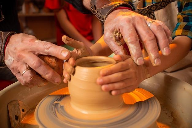 De handen van de pottenbakker en de handen van het kind werken met klei op een speciale machine.