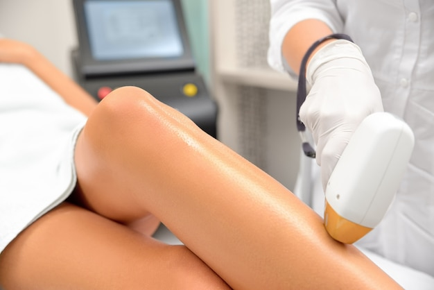 De handen van de schoonheidsspecialist maken het epileren van de benen