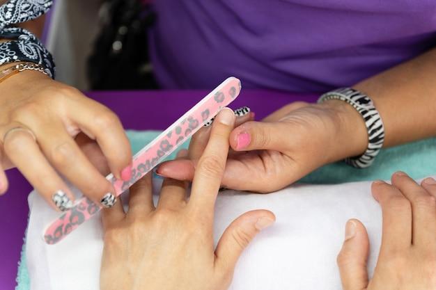 De handen van de schoonheidsspecialiste die de nagels van een cliënt indienen