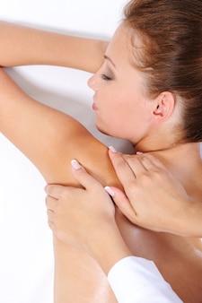 De handen van de schoonheidsspecialiste die jonge vrouw een massage op haar schouder geven