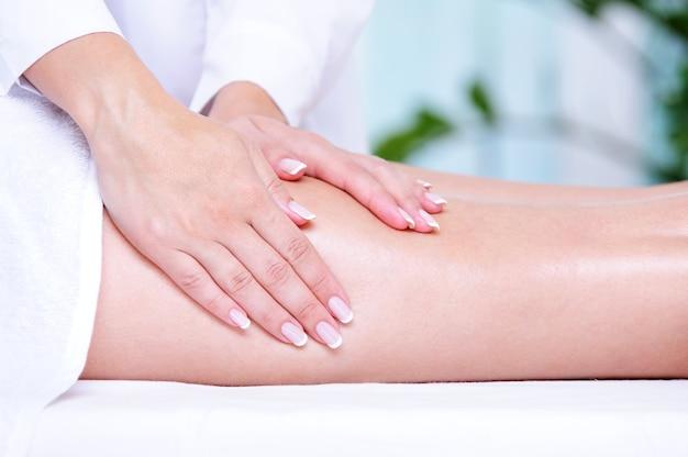 De handen van de schoonheidsspecialiste die massage voor het vrouwelijke been doen