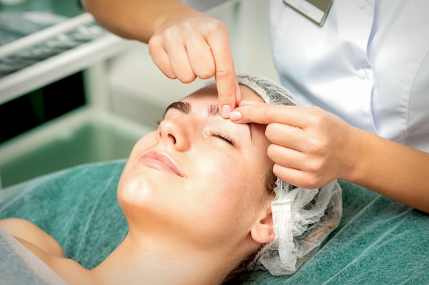 De handen van de schoonheidsspecialiste maken massage op de wenkbrauw voor een vrouw terwijl een gezichtsmassage in het centrum van de cosmetologie kliniek