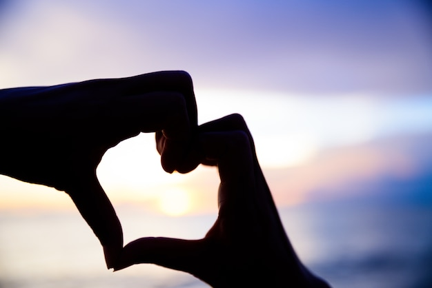 De handen van de silhouetvrouw om hartvorm op zonsondergangachtergrond te zijn.