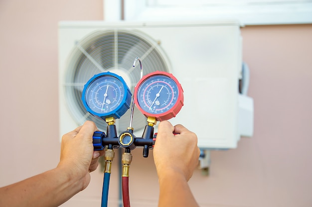 De handen van de technicus gebruiken een meetinstrument om te controleren dat de vacuümpomp de lucht naar de airconditioning afvoert.