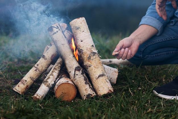 De handen van de toerist steken een brand in de bergen aan