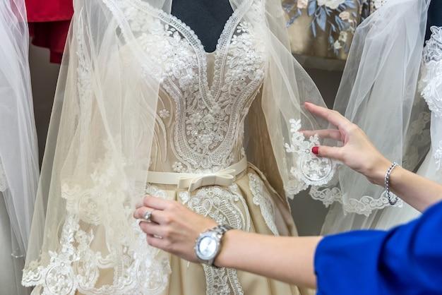 De handen van de verkoper corrigeren bruidssluier op etalagepop in salon