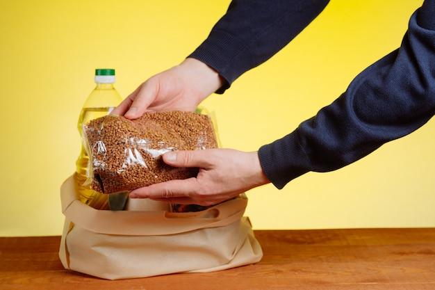 De handen van de vrijwilliger stopten de eerste levensbehoeften in een tas voor donaties aan ouderen.