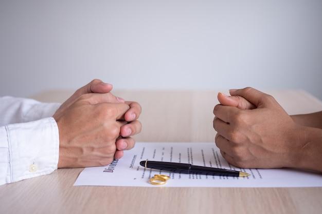 De handen van de vrouw en man rusten op de echtscheidingsdocumenten. het indienen van echtscheidingsdocumenten of huwelijkse voorwaarden opgesteld door een advocaat. de trouwring vertegenwoordigt het verbond van geliefden.
