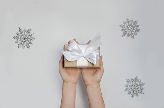 De handen van de vrouw geven huidige doos op wit. cadeau met wit lint.