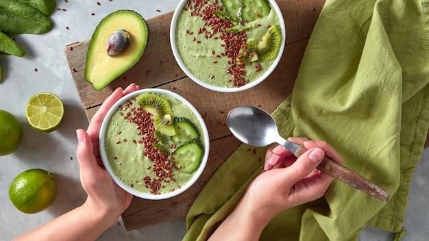 De handen van de vrouw houden een lepel en een bord vast met gezonde smoothies van komkommer, asperges, avocado met stukjes kiwi en vlas op een grijze keukentafel. bovenaanzicht