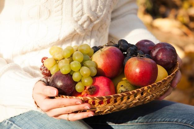 De handen van de vrouw houden een mand met vers fruit vast. detailopname