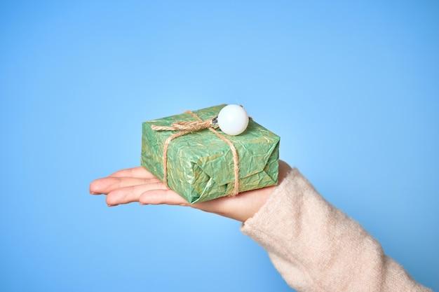 De handen van de vrouw houden geschenkdozen. kerst of nieuwjaar versierde geschenkdoos.