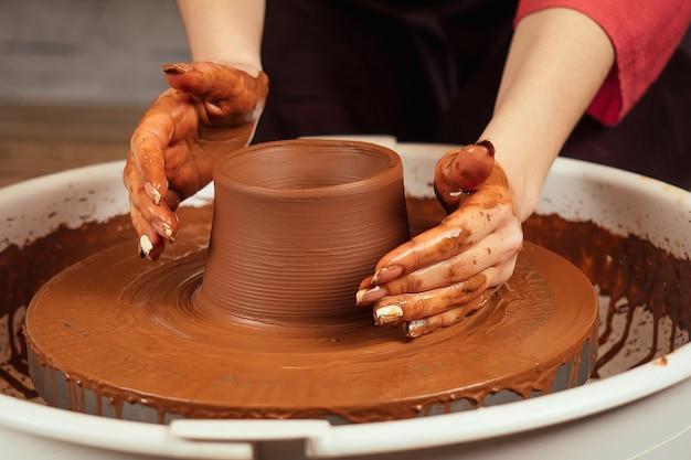 De handen van de vrouw in de klei op de pottenbakkersschijf vormen een vaas. de pottenbakker werkt in een pottenbakkerij met klei. het concept van aardewerk meesterschap en creativiteit.