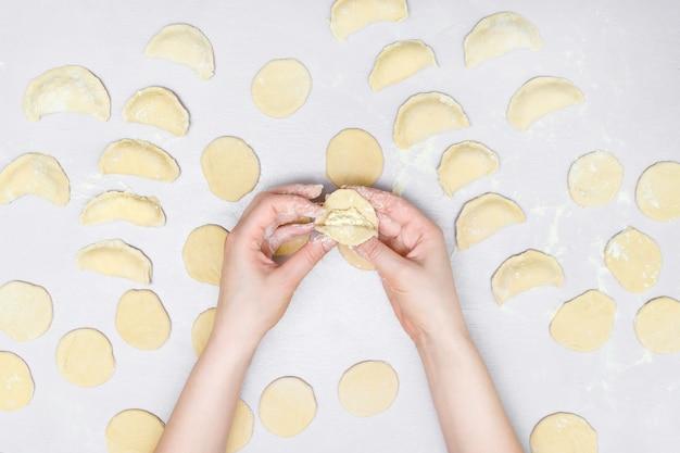 De handen van de vrouw maken ravioli