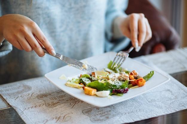 De handen van de vrouw met caesar-salade op lijst in restaurant