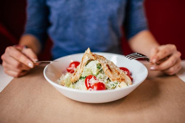 De handen van de vrouw met salade caesar op lijst in restaurant