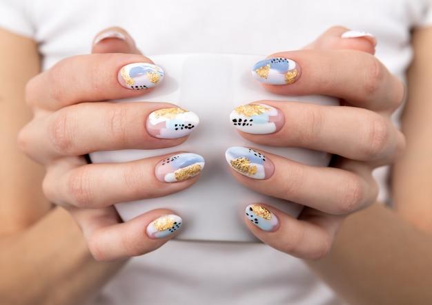 De handen van de vrouw met trendy pastelkleurnagels die kop houden