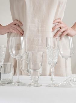 De handen van de vrouw met verschillende wijnglazen op de lijst aangaande het wit
