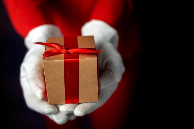 De handen van de vrouw met witte handschoenen met geschenkdozen