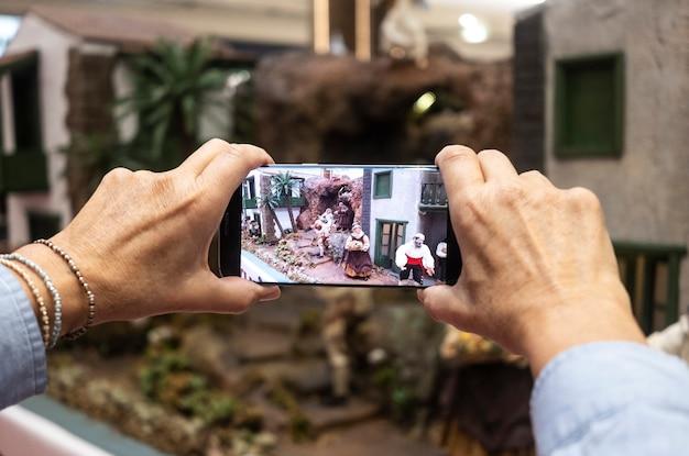De handen van de vrouw nemen een foto van de kerststal in het winkelcentrum - concept van kerstvakantie