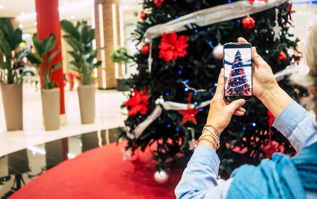 De handen van de vrouw nemen een foto van de prachtige kerstboom in het winkelcentrum - concept van vakantie en consumentisme