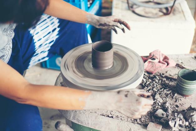 De handen van de vrouw sluiten zich op, het meesterlijke atelier van keramiek werkt met klei