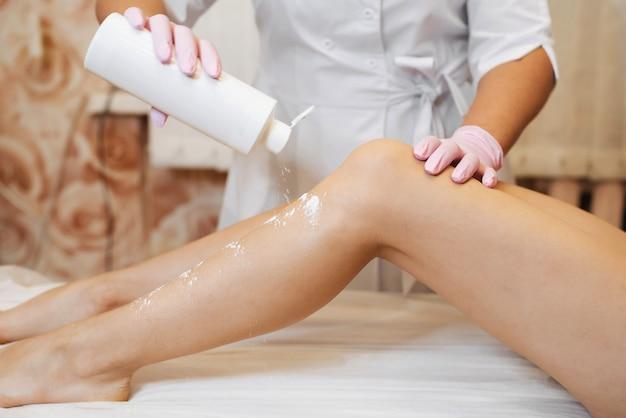 De handen van de vrouw van een schoonheidsspecialist die slanke vrouwelijke benen voorbereidt op de procedure van het verwijderen van suikerhaar
