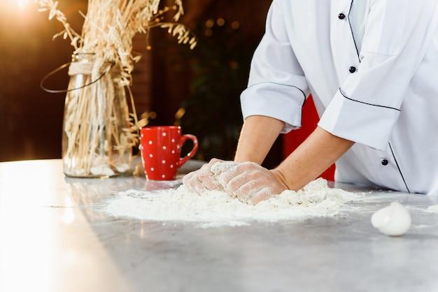 De handen van de vrouwelijke bakker het kneden van deeg op de lijst met bloem, eieren en andere ingrediënten.