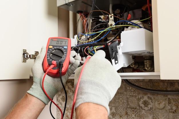 De handen van de werknemer controleren de bruikbaarheid van de elektronica van de gasboiler