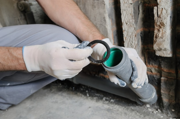 De handen van de werknemer installeren rioolbuizen.