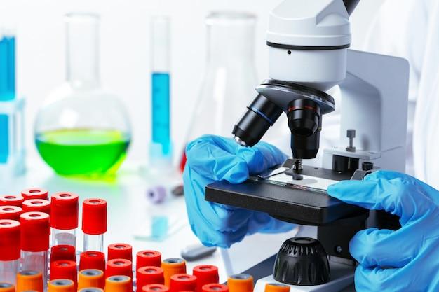 De handen van de wetenschapper die chemisch onderzoek doen met behulp van een microscoop