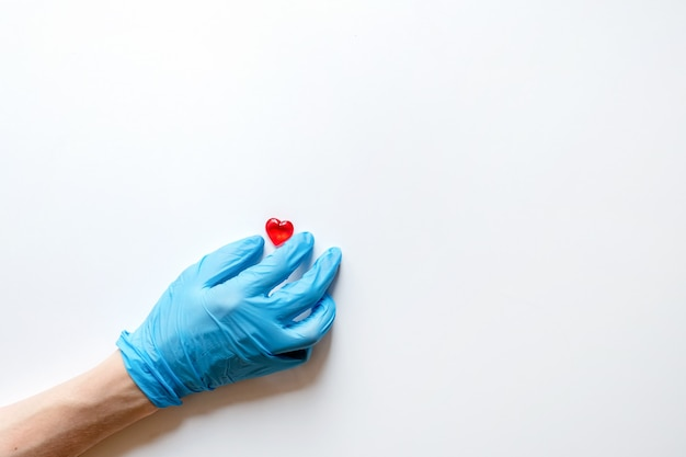 De handen van een arts in medische handschoenen op een witte ondergrond met steen in de vorm van een hart